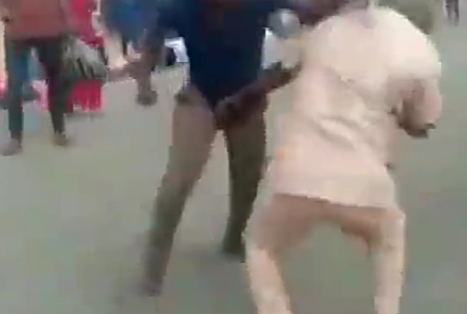 Two grown men fight over a woman in the middle of a street in Nigeria while spectators watch (video)
